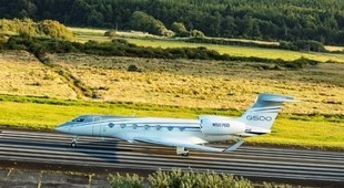 Gulfstream G500 on runway surrounded by fields