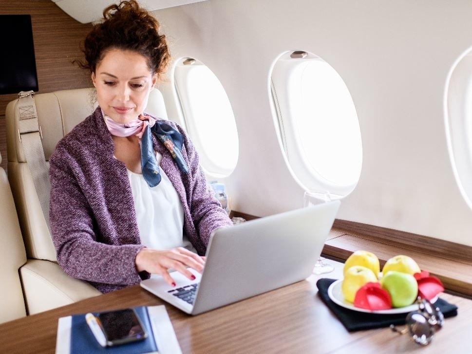 Businesswoman Enjoys Private Jet Cabin Connectivity