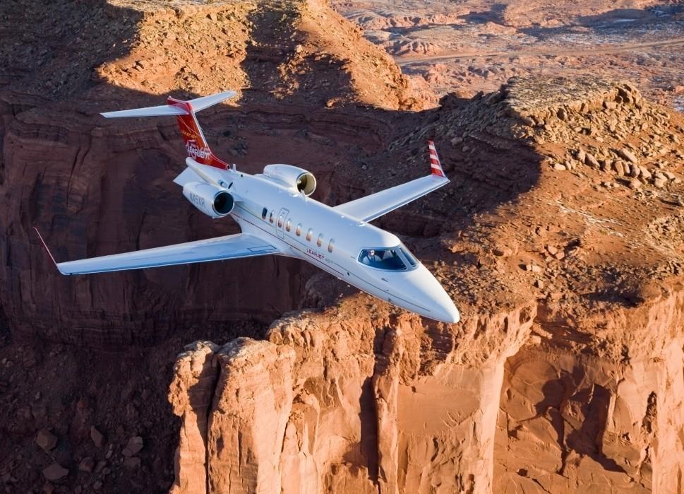 Bombardier Learjet 45XR flies over rocky terrain