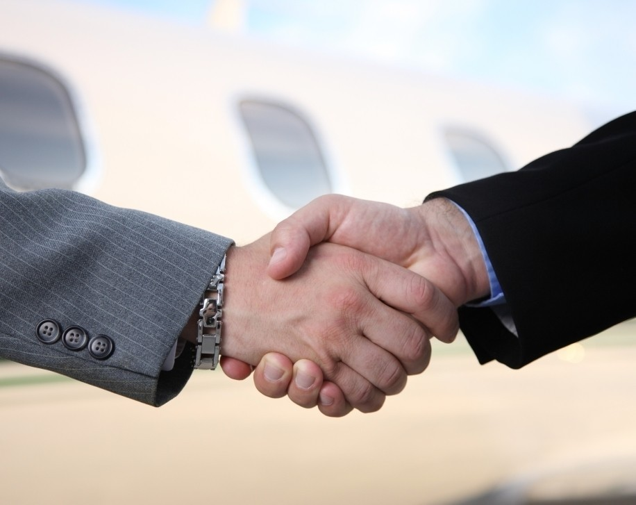 Buyer and Seller Shake Hands in Front of Private Jet