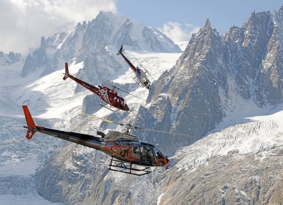 Airbus H125 Helicopters Fly in Formation Near Mountain Face