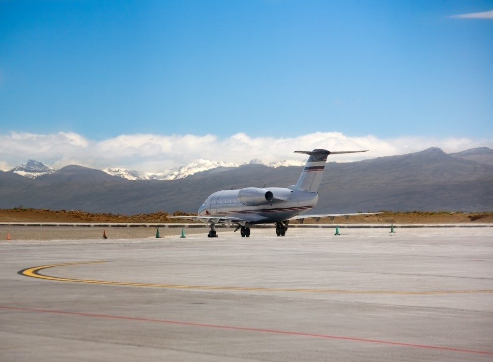 Private jet stands alone at an airport surrounded by mountains