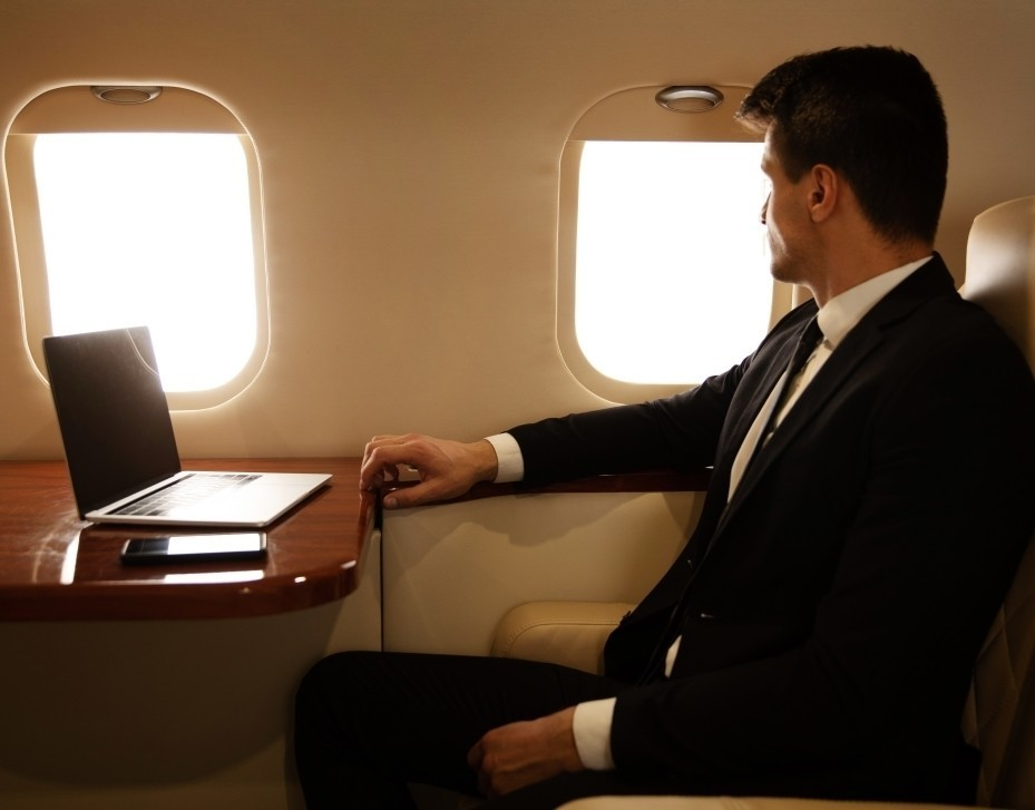 Businessman looks out of private jet window