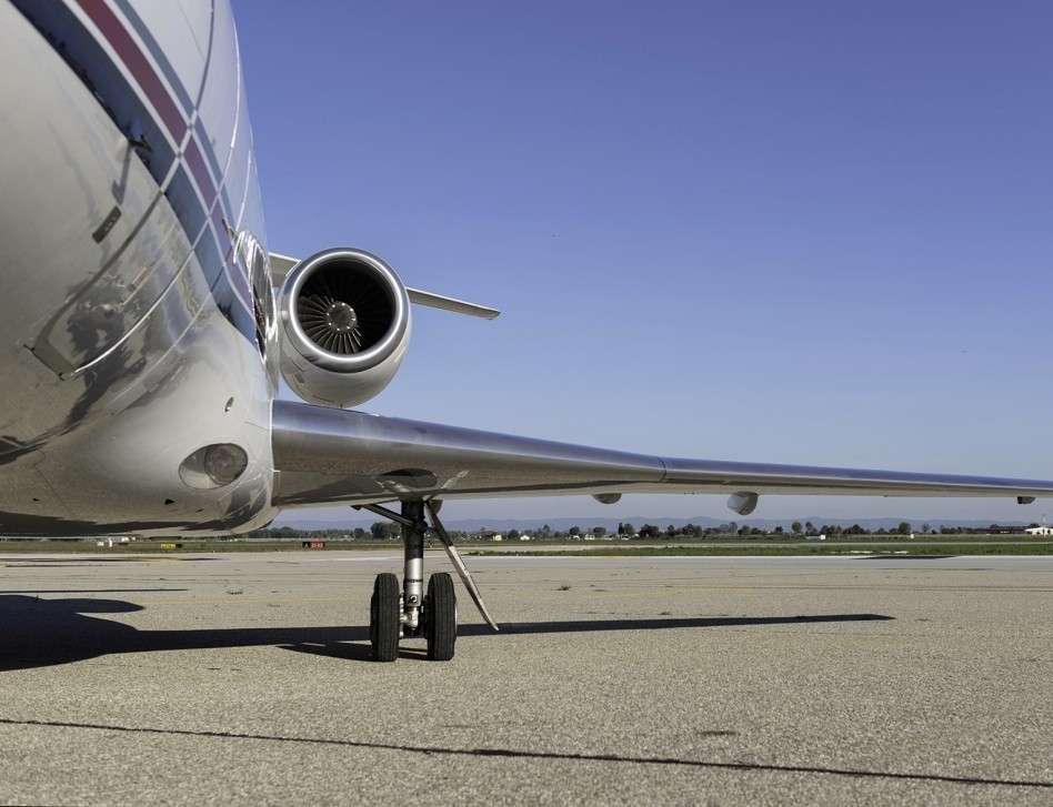 Private Jet parked on airport ramp focus on wing and engine
