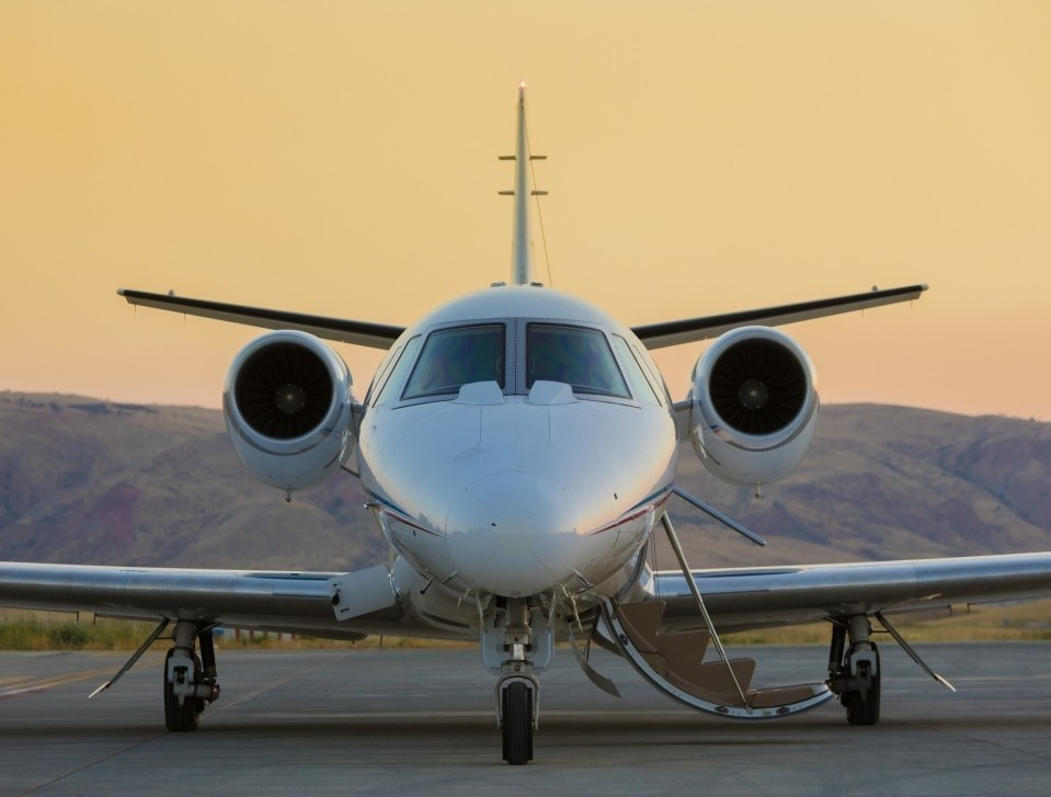 Front view of a private jet on ramp at sunset