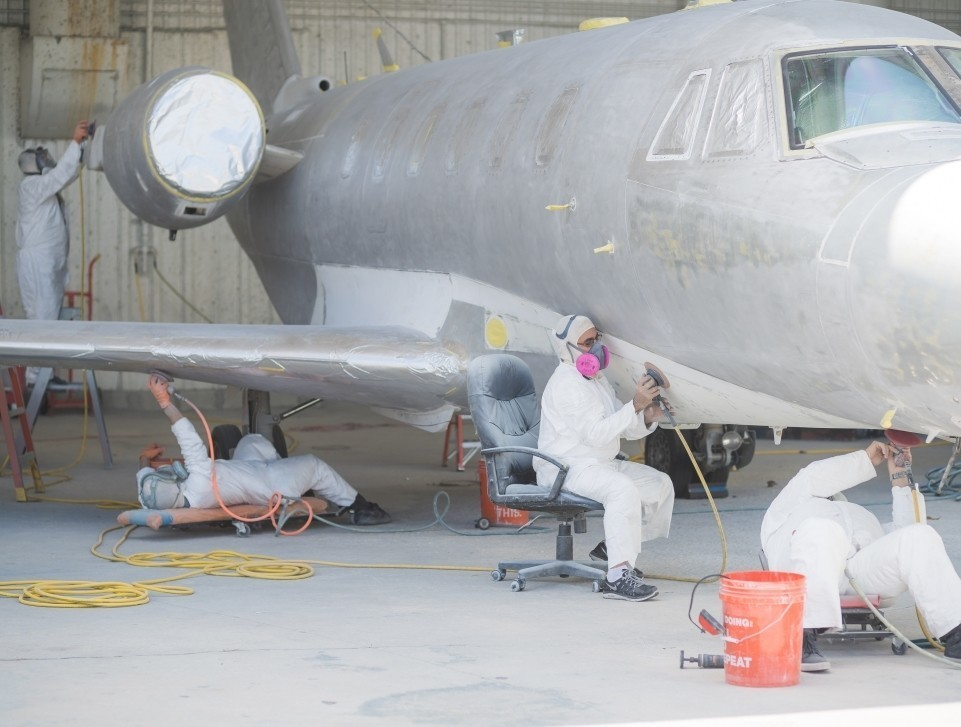 An MRO shop's paint team work on the body of a private jet