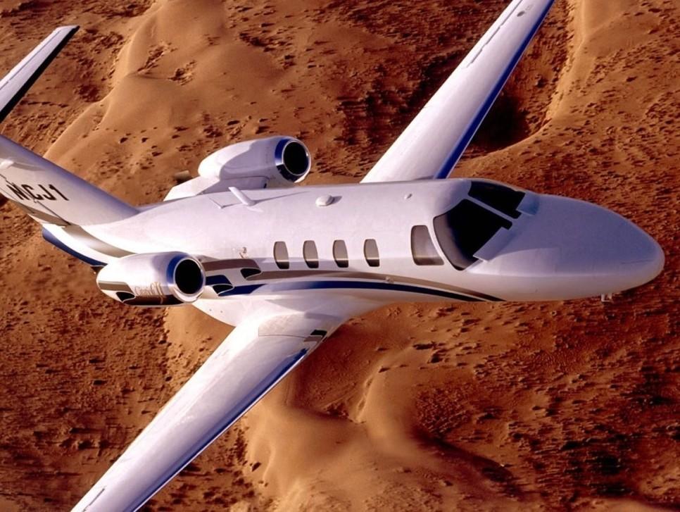 Cessna Citation CJ1 private jet flies across desert terrain