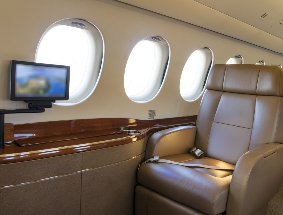 Large business jet cabin with empty seat and monitor