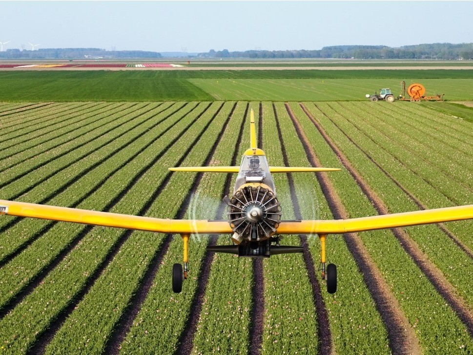 Agricultural turboprop aircraft crop dusting a field
