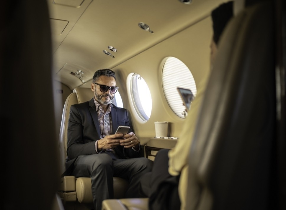 Executives on a Beechcraft King Air use their phones in-flight