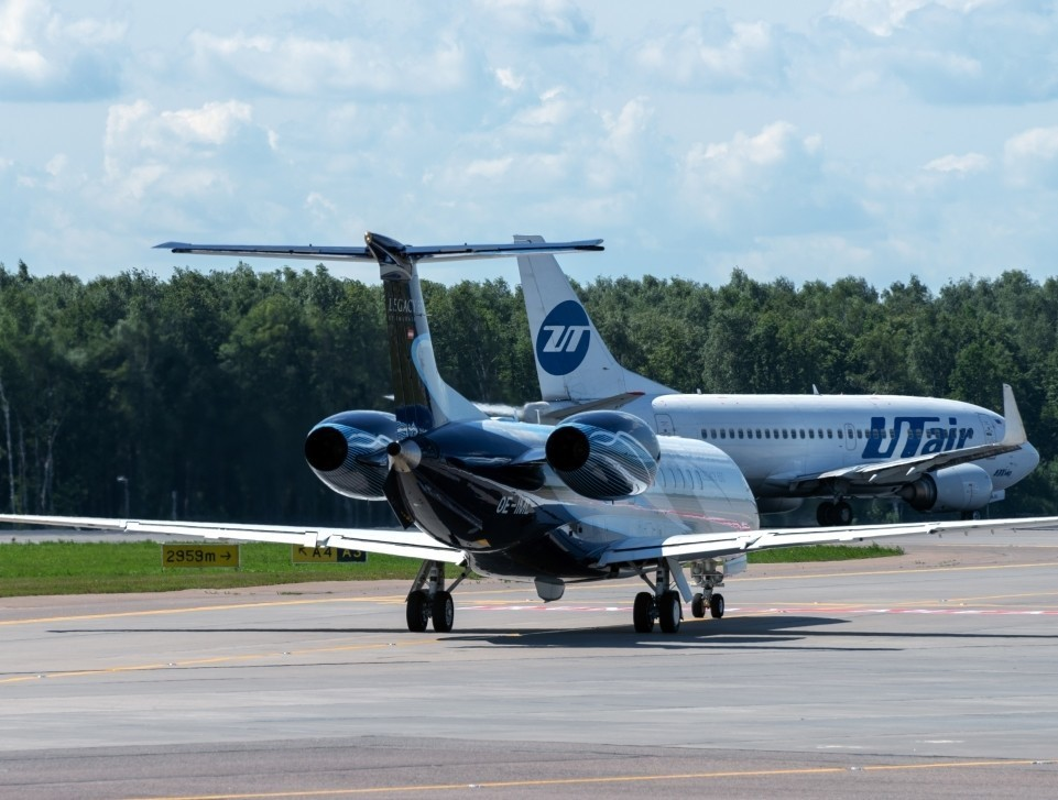 An Embraer Legacy 650 private jet waits on the airport taxiway