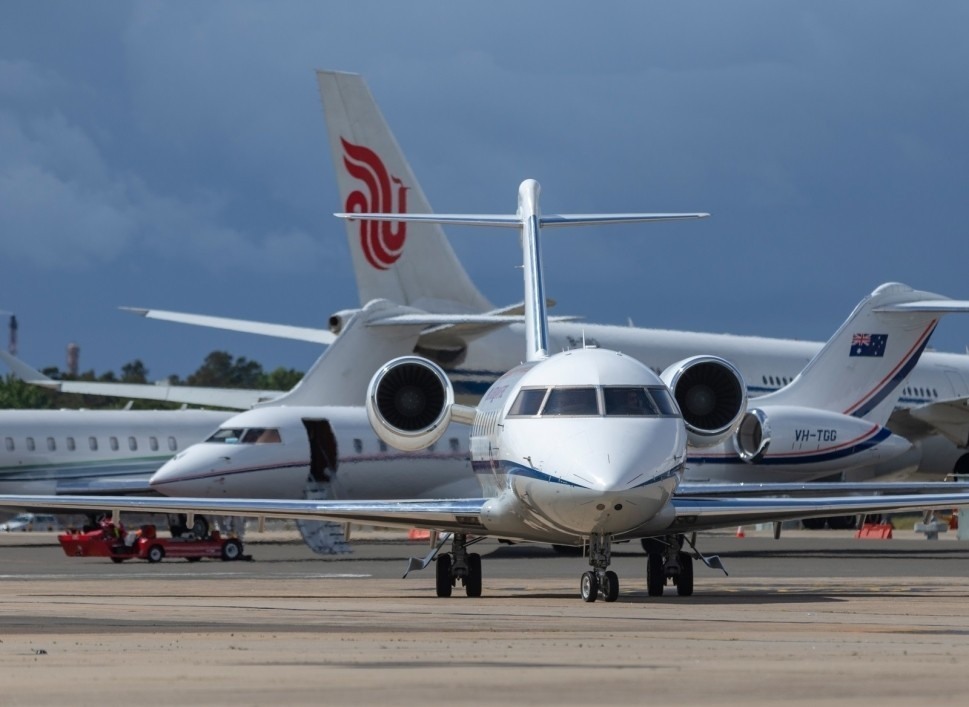 Bombardier Challenger private jet on a crowded airport ramp