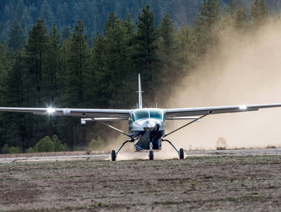 A Cessna Grand Caravan EX takes off from a remote dirt airstrip