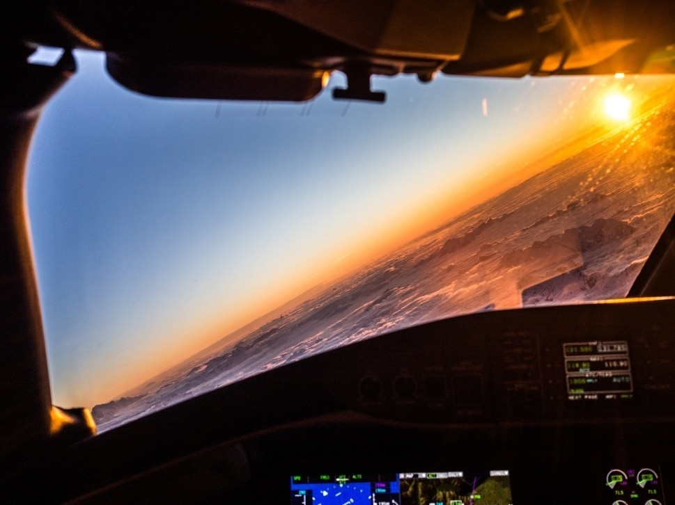 Sunset over clouds outside a private jet cockpit window