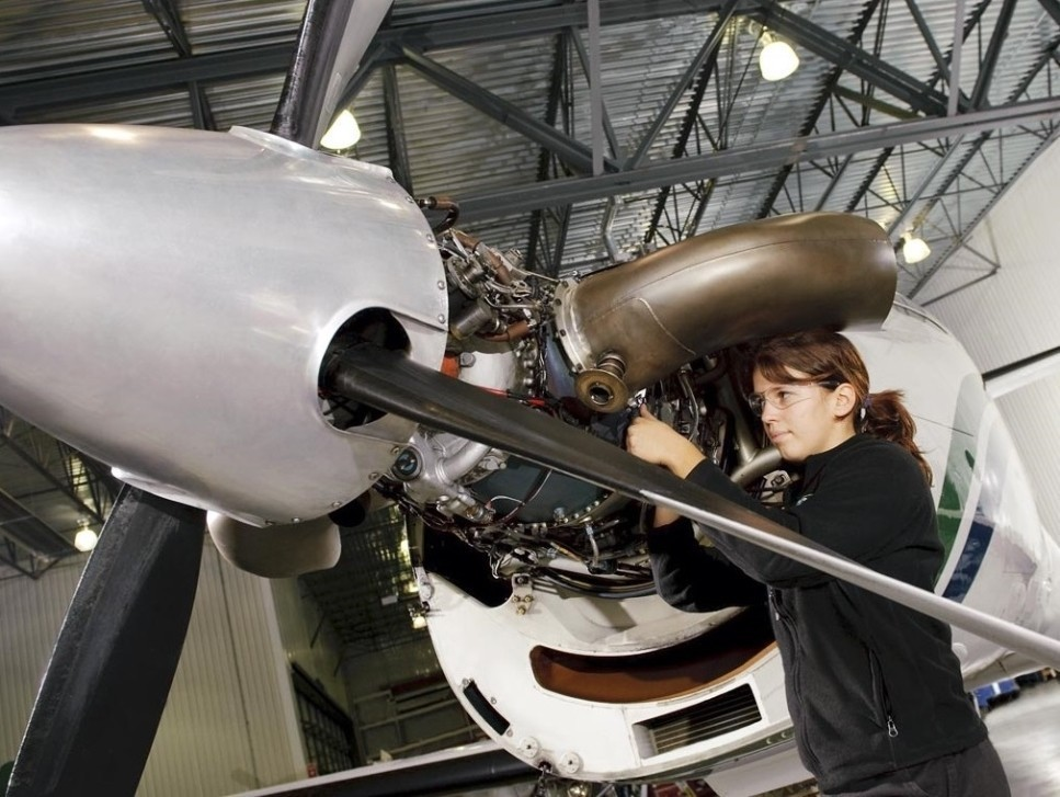 Young Pratt & Whitney mechanic works on a PT6A turboprop engine