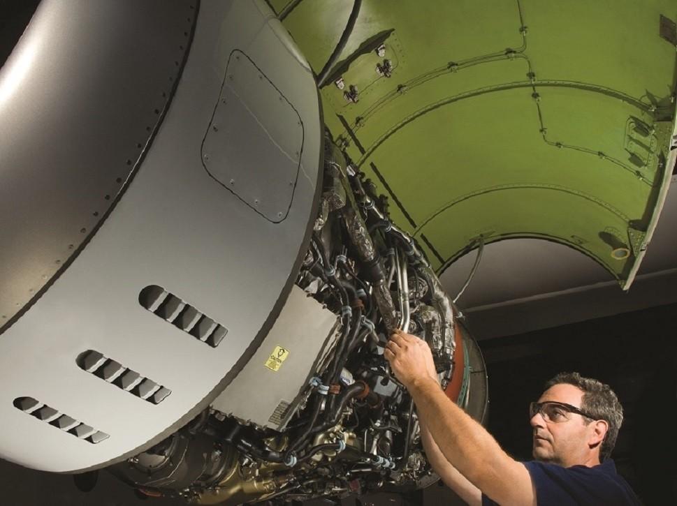 MRO worker performing maintenance on a Pratt & Whitney jet engine