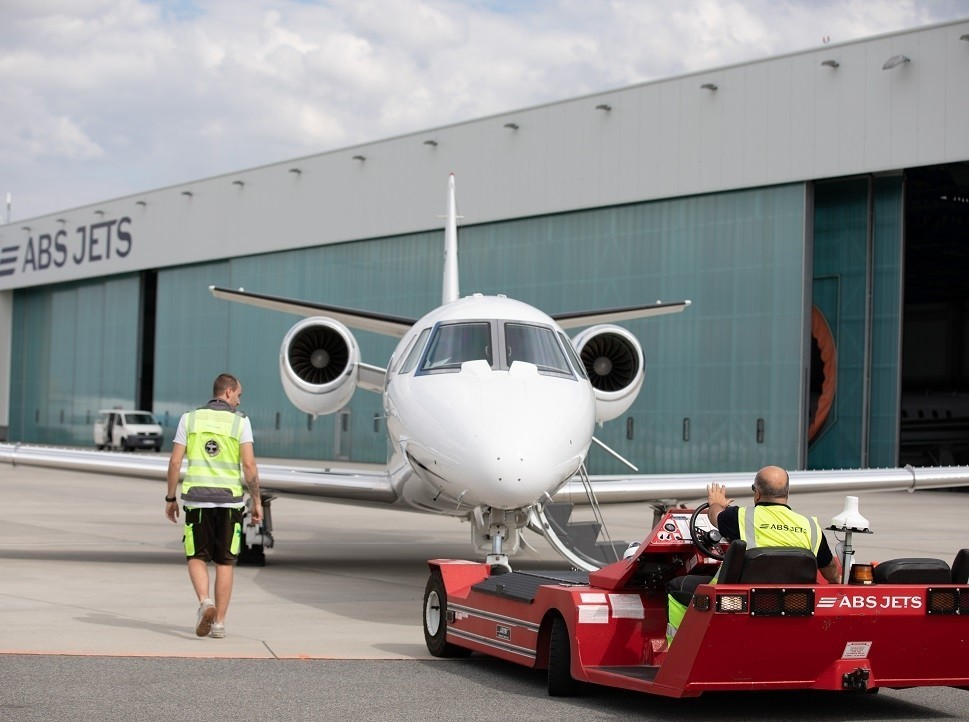 ABS Jets tug prepares to tow a private jet into the maintenance hangar