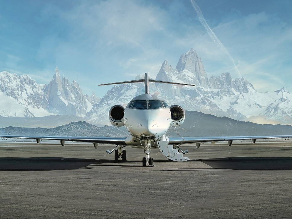 Snowy mountain range behind a parked private jet