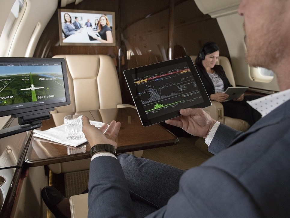 Busy executive using a private jet cabin management system