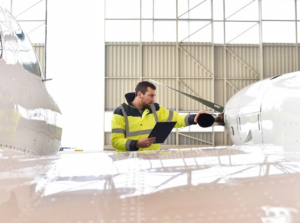 A mechanic refers to a checklist as he inspects a turboprop engine