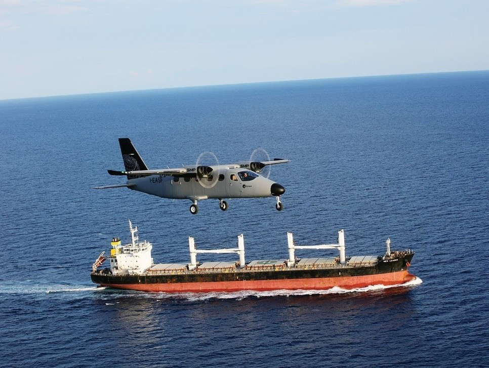 An aerial Surveillance aircraft flies by an oil tanker at sea