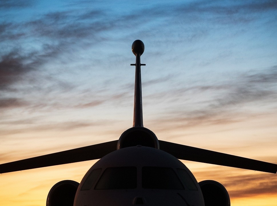 A Dassault Falcon tri-jet silhouetted against sunset sky