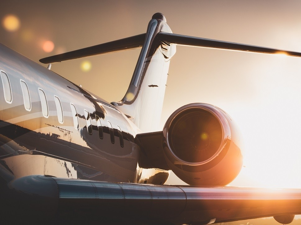 Private Bombardier Global business jet over-wing view with sunset