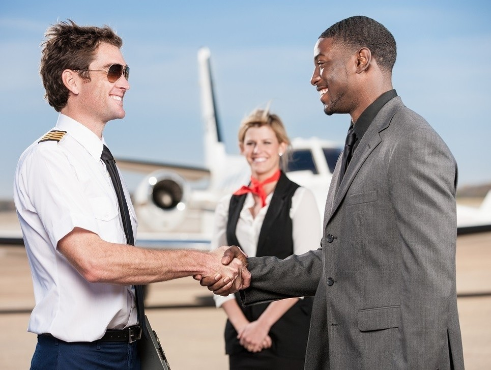 A private jet passenger welcomed by the pilot and stewardess