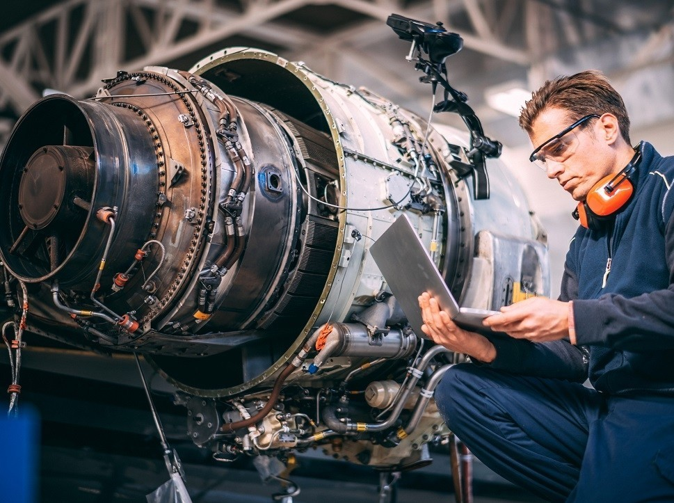Airplane mechanic with digital maintenance records next to private jet