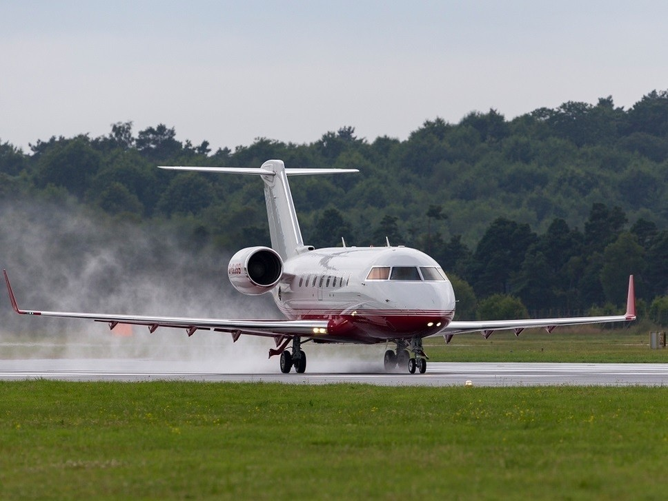 Bombardier Challenger 605 jet touches down in the rain