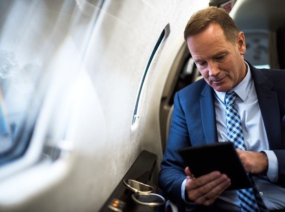 Businessman with iPad in private jet cabin