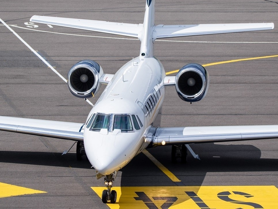 A private jet moves along an airport taxiway