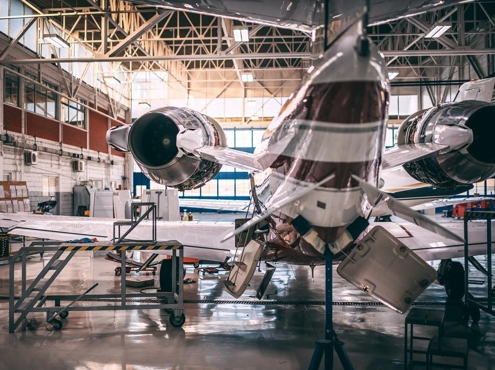A private jet undergoes maintenance in an MRO shop hangar
