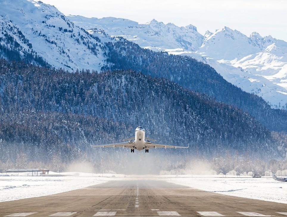 A private jet takes off from airport set within mountains