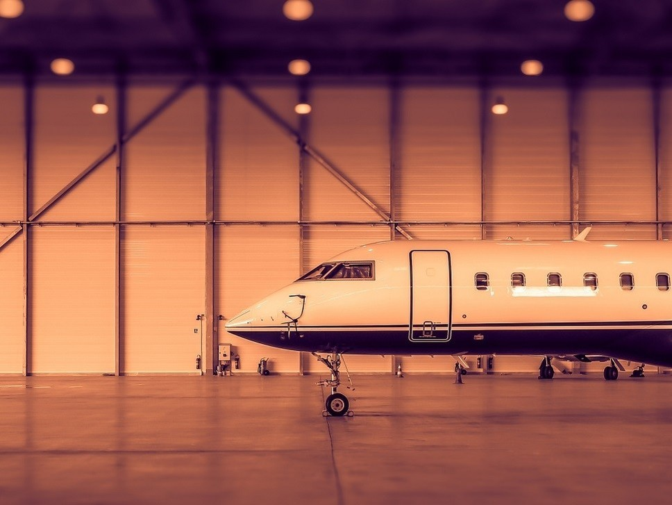 A Bombardier private jet parked in an empty hangar