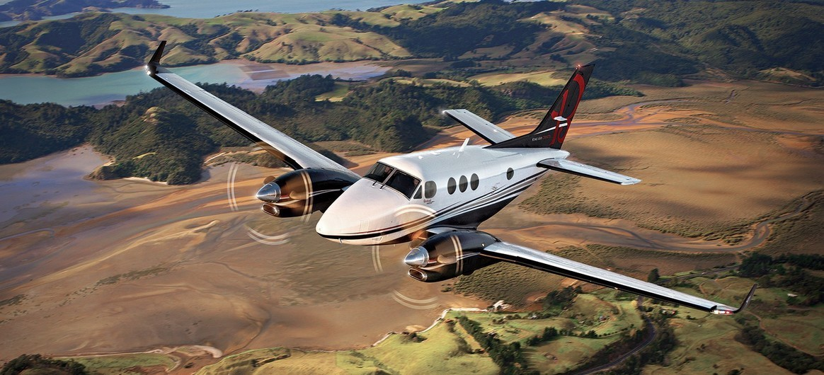 King Air C90GTx flying over fields