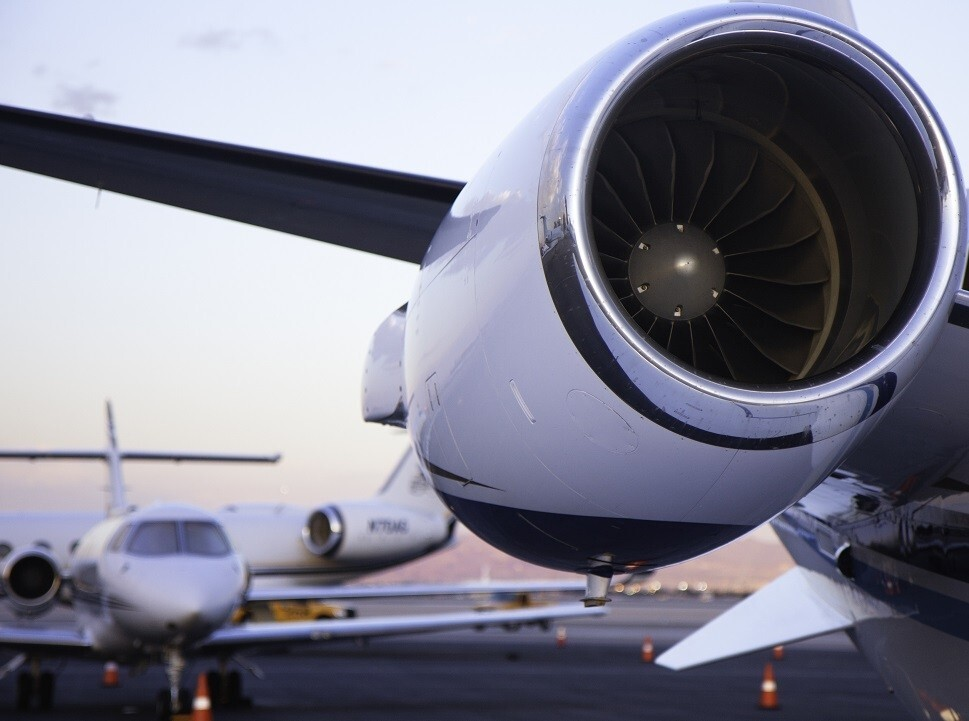 Jet engine (foreground) with other private jets parked at airport