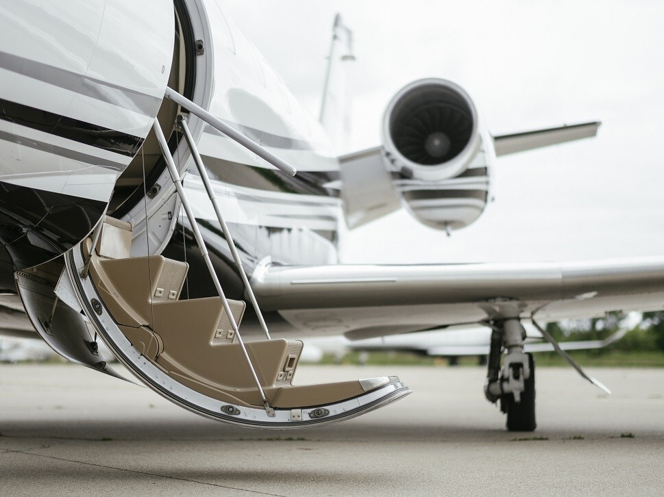 A private jet waits with an open door to pick up passengers