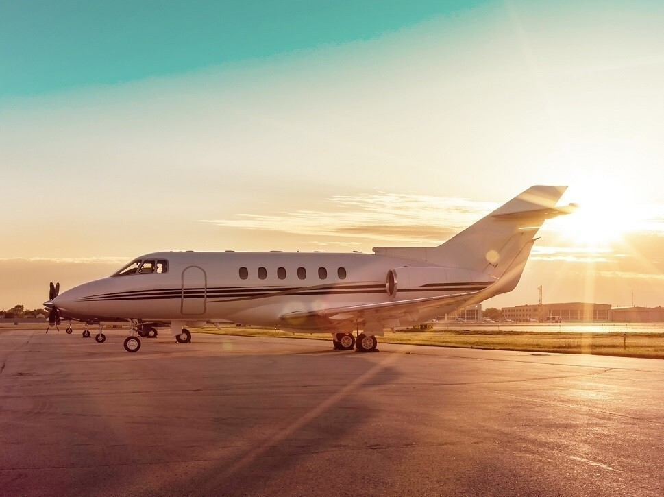 A Hawker 800-series private jet on airport ramp at sunrise