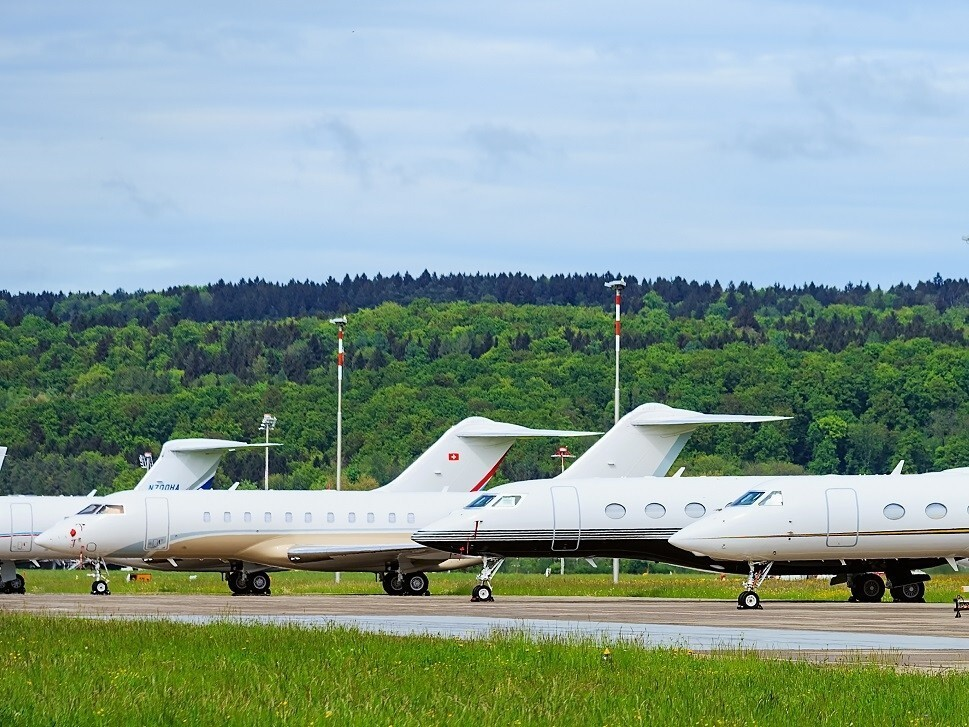 Private jets parked in a row on airport ramp