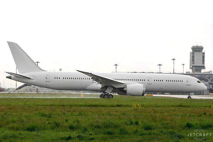 2015 boeing 787-9 on airfield with grass verges communications tower in background grey sky
