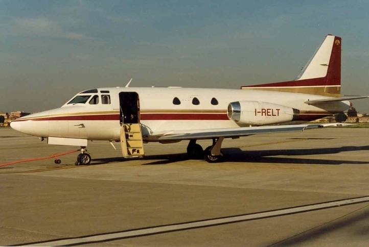1974 sabreliner 40 parked on sunny airfield side view of aircraft paintwork white with maroon and gold stripes