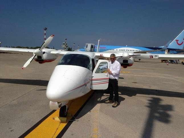 2009 tecnam p2006 parked on airifeld with large aircraft in view man standing nexto plane with cockpit door opne white body work with red and grey stripes