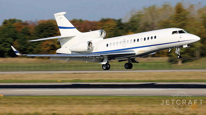2012 dassault falcon 7x in motion on runway white body work with blue accent stripes