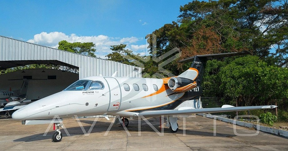 2011 embraer phenom 100 parked in front of hangar