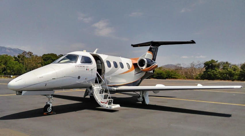 2010 embraer phenom 100 parked on runway