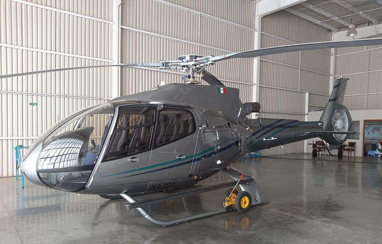 grey eurocopter ec130b4 with green and blue stripes along the fuselage to vertical fin inside hangar