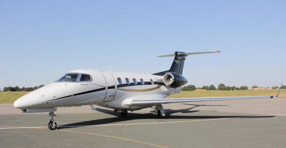 2014 embraer phenom 300 parked on runway apron