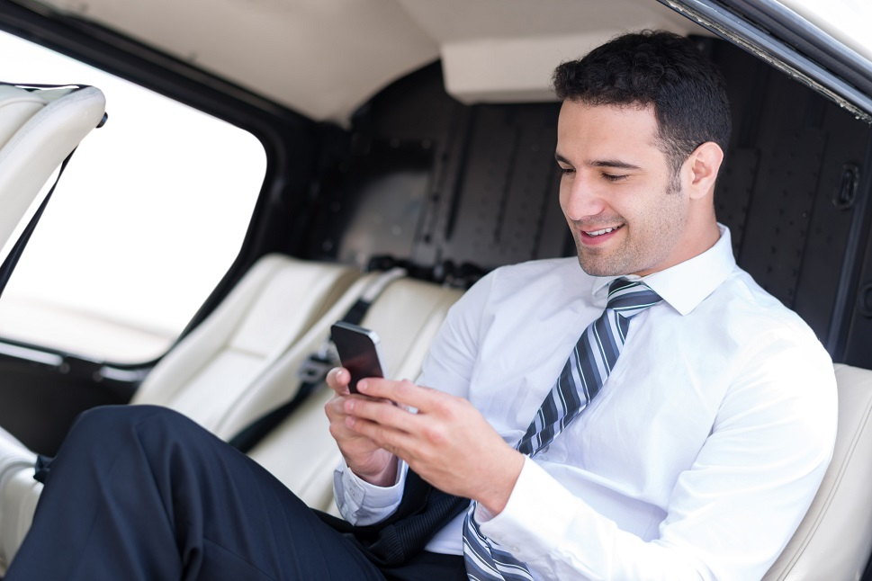 A young businessman sitting is a single-engine turbine helicopter cabin