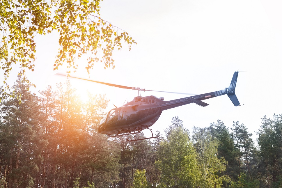A turbine helicopter takes off from a woodland clearing